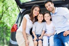 Familia de cuatro miembros que se sienta en tronco de coche Imagenes de archivo