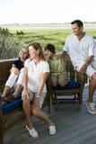 Familia de cuatro miembros que se sienta junto al aire libre en terrac Imagen de archivo