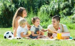 Familia de cuatro miembros que tiene comida campestre Foto de archivo libre de regalías