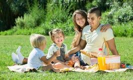 Familia de cuatro miembros que tiene comida campestre Imágenes de archivo libres de regalías