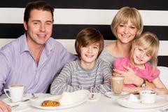 Familia de cuatro miembros que tiene gran tiempo en restaurante fotografía de archivo