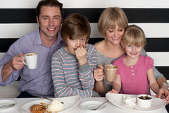 Familia de cuatro miembros que tiene gran tiempo en restaurante imágenes de archivo libres de regalías