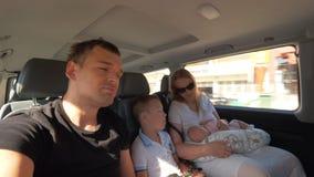 Familia de cuatro miembros que viaja en coche en la ciudad almacen de metraje de vídeo