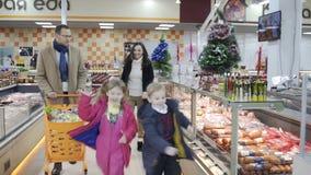 Familia de cuatro miembros sonriente que disfruta de hacer compras junto Cámara lenta almacen de video