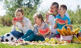 Familia de cuatro miembros sonriente que tiene comida campestre y consumición de la sandía Imagenes de archivo