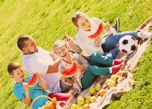 Familia de cuatro miembros sonriente que tiene comida campestre y consumición de la sandía Foto de archivo