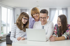 Familia de cuatro miembros usando el ordenador portátil junto en la tabla en hogar Fotografía de archivo libre de regalías