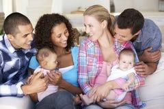 Familia de dos jóvenes con los bebés en Sofa At Home Fotografía de archivo