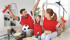 Familia de fans que miran un partido de fútbol en la TV en casa Imagen de archivo