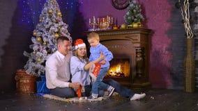 Familia de Joyfull de tres personas debajo del árbol de navidad HD almacen de metraje de vídeo