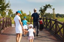 Familia de jugadores de golf que caminan en el curso Imagen de archivo libre de regalías