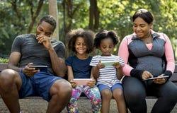 Familia de la ascendencia africana junto que se sienta en un banco en el parque Imagen de archivo libre de regalías