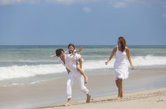 Familia de la madre, del padre y del niño que corre divirtiéndose en la playa Imagenes de archivo