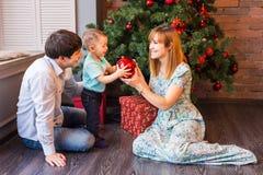 Familia de la Navidad con el niño Padres felices y niños sonrientes en casa que celebran Año Nuevo Árbol de navidad Fotos de archivo