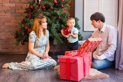 Familia de la Navidad con el niño Padres felices y niños sonrientes en casa que celebran Año Nuevo Árbol de navidad Fotos de archivo libres de regalías
