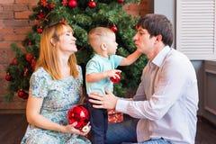 Familia de la Navidad con el niño Padres felices y niños sonrientes en casa que celebran Año Nuevo Árbol de navidad Imagen de archivo libre de regalías