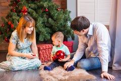 Familia de la Navidad con el niño Padres felices y niños sonrientes en casa que celebran Año Nuevo Árbol de navidad Foto de archivo libre de regalías