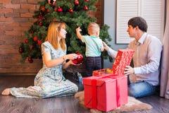 Familia de la Navidad con el niño Padres felices y niños sonrientes en casa que celebran Año Nuevo Árbol de navidad Imagen de archivo