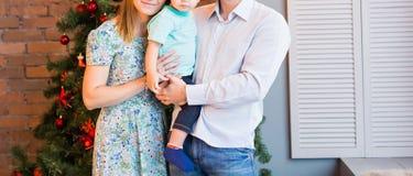 Familia de la Navidad con el niño Padres felices y niños sonrientes en casa que celebran Año Nuevo Árbol de navidad Foto de archivo