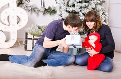 Familia de la Navidad con los regalos de la abertura del bebé Feliz Foto de archivo libre de regalías