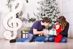 Familia de la Navidad con los regalos de la abertura del bebé Feliz Fotografía de archivo libre de regalías