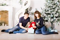 Familia de la Navidad con los regalos de la abertura del bebé Feliz foto de archivo