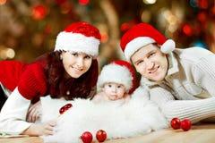 Familia de la Navidad de personas del tres en sombreros rojos fotografía de archivo libre de regalías