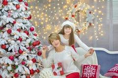 Familia de la Navidad junto cellebrating la hija y la madre del Año Nuevo del día de fiesta cerca del árbol blanco de Navidad con Imagen de archivo