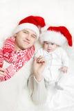 Familia de la Navidad: padre y bebé en sombreros rojos. imágenes de archivo libres de regalías