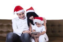 Familia de la Navidad usando una tableta Foto de archivo libre de regalías