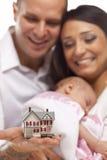 Familia de la raza mezclada con la casa del pequeño modelo Fotografía de archivo libre de regalías