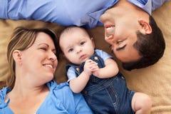 Familia de la raza mezclada en una manta Foto de archivo