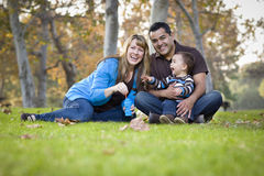 Familia de la raza mezclada que juega con las burbujas en parque Fotos de archivo