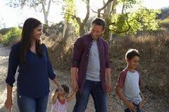 Familia de la raza mixta que camina en la trayectoria rural, vista delantera retroiluminada imagenes de archivo