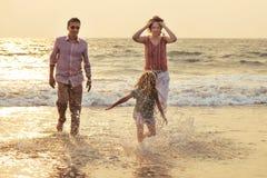 Familia de la raza mixta que juega con el niño en el mar en la puesta del sol fotografía de archivo