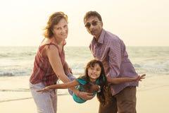 Familia de la raza mixta que juega con el niño en el mar en la puesta del sol foto de archivo libre de regalías
