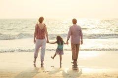 Familia de la raza mixta que juega con el niño en el mar en la puesta del sol imagenes de archivo