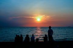 familia de la reunión de la silueta que mira puesta del sol en la playa Fotos de archivo