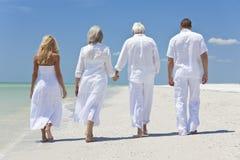 Familia de las generaciones de los mayores de la gente que recorre en la playa Imagenes de archivo