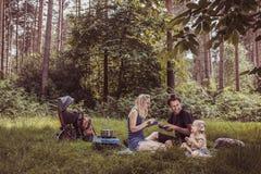 Familia de los Backpackers que cena en naturaleza Foto de archivo libre de regalías