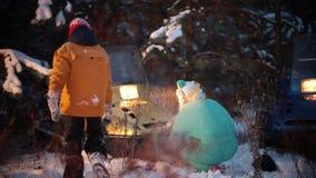 Familia de los jóvenes del bosque del invierno que juega con nieve en el bosque por el fuego metrajes