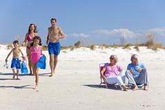 Familia de los niños y de los abuelos de los padres en la playa Imagen de archivo libre de regalías