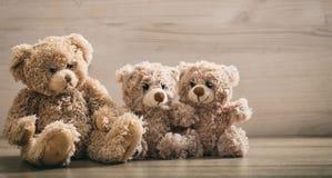Familia de los osos de peluche que se sienta en un fondo de madera Imagen de archivo libre de regalías