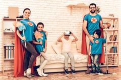 Familia de los super héroes que mira al niño que juega las auriculares de VR foto de archivo
