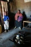 Familia de Maasai dentro de sus chozas, una mujer negra y niños Imagen de archivo