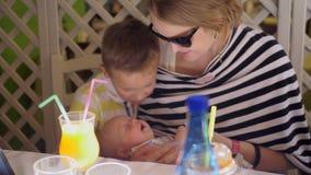 Familia de madre con dos niños que disfrutan del tiempo junto almacen de video