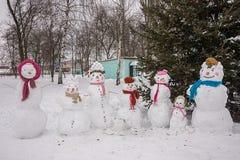 Familia de muñecos de nieve en el festival del invierno del ` s de los niños, en un sombrero y una bufanda Foto de archivo libre de regalías