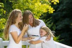 Familia de muchachas que disfrutan de un momento junto mientras que come el franco fresco Imágenes de archivo libres de regalías