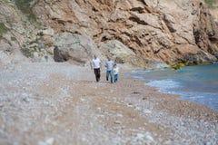 Familia de padre de abuelo y de hijo en una playa rocosa el vacaciones que disfrutan del tiempo junto Fotografía de archivo libre de regalías