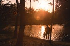 Familia de padres papá y de siluetas de los niños de la hija en el fondo hermoso del aire libre de la naturaleza de la puesta del imagen de archivo
